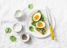 Heerlijk gezond ontbijt - geroosterde broodsandwich met spinazie en gekookte eieren op witte achtergrond Stock Foto's