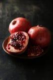 Heerlijk granaatappelfruit op plaat op de zwarte achtergrond stock afbeeldingen