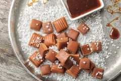 Heerlijk karamelsuikergoed, saus en zout op plaat stock foto