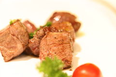Heerlijk kubiek rundvleeslapje vlees op een witte schotel stock foto