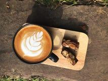 Heerlijk Ontbijt; De koffie van de Lattekunst in Zwarte kop en Brownie die met gesneden amandel wordt bedekt royalty-vrije stock fotografie