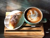 Heerlijk Ontbijt; de kunstkoffie van Latte van de zwaanvorm in Groen en wit kop en Croissant royalty-vrije stock foto's