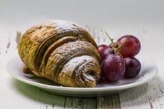Heerlijk ontbijt met verse croissants en rijpe bessen op oude houten achtergrond, selectieve nadruk Royalty-vrije Stock Afbeeldingen