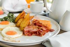 Heerlijk op de ochtend Het ontbijt bestaat uit eieren, bacon, worst, bacon, aardappel en spinazie met kaas royalty-vrije stock foto