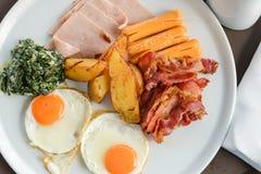 Heerlijk op de ochtend Het ontbijt bestaat uit eieren, bacon, worst, bacon, aardappel en spinazie met kaas stock afbeeldingen