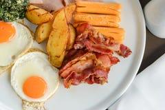 Heerlijk op de ochtend Het ontbijt bestaat uit eieren, bacon, worst, bacon, aardappel en spinazie met kaas royalty-vrije stock fotografie
