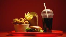 Heerlijk snel die voedsel op rode achtergrond, het goedkope hoge calorie eten wordt verlicht stock footage