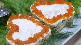 Heerlijk voedsel op de lijst Sandwiches met rode kaviaar in de vorm van een hart en met dille op plaat en bladen van stock video