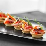 Heerlijk voorgerecht met ham, kaas, peper en tomaat in tartlets Concept voedsel, restaurant, catering, menu stock fotografie