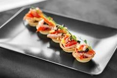 Heerlijk voorgerecht met ham, kaas, peper en tomaat in tartlets Concept voedsel, restaurant, catering, menu royalty-vrije stock foto