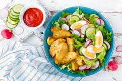Heerlijke aardappel in de schil, gekookt ei en verse groentesalade van sla, komkommer en radijs De zomermenu voor detoxdieet stock afbeeldingen