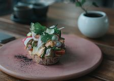 Heerlijke avocadotoost met artisanaal brood op een roze plaat royalty-vrije stock afbeeldingen