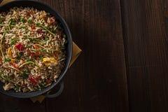 Heerlijke Aziatische rijst op een zwart gietijzer met hout Royalty-vrije Stock Fotografie