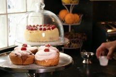 Heerlijke bevroren broodjes in bakkerij met eigengemaakte cake en suikerglazuur op achtergrond royalty-vrije stock foto's