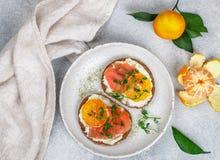 Heerlijke broodtoosts met roomkaasricotta, gezouten gerookte zalm, mandarijn en erwtenspruiten royalty-vrije stock fotografie