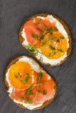 Heerlijke broodtoosts met roomkaasricotta, gezouten gerookte zalm, mandarijn en erwtenspruiten royalty-vrije stock afbeeldingen