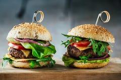 Heerlijke burgers met rundvlees, tomaat, kaas en sla Royalty-vrije Stock Afbeelding