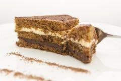 Heerlijke chocoladecake, die door een glanzende lepel wordt verdeeld; close-up op een witte achtergrond royalty-vrije stock afbeelding