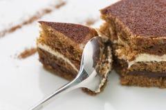 Heerlijke chocoladecake, die door een glanzende lepel wordt verdeeld; close-up op een witte achtergrond royalty-vrije stock foto's