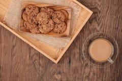 Heerlijke chocoladeschilferkoekjes op een dienblad op donker oud houten Ta stock fotografie