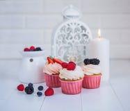 Heerlijke cupcakes met bessen op een witte achtergrond Stock Fotografie