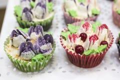 Heerlijke cupcakes met buttercream en vruchten Stock Afbeeldingen