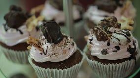 Heerlijke cupcakes met chocolade op een tribune stock footage