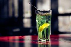 Heerlijke de zomerdrank met een plak van citroen op de rode lijst royalty-vrije stock afbeelding