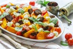 Heerlijke de zomersalade van gele en rode tomaten, croutons, kaasmozarella, Basilicum Stock Foto