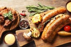Heerlijke die maaltijd voor barbecuepartij wordt gediend op houten lijst stock afbeelding