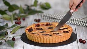 Heerlijke Eigengemaakte Cherry Pie met een Vlokkige Korst die een kersenpastei snijden stock video