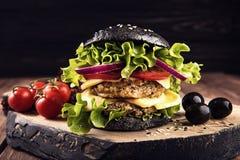Heerlijke eigengemaakte veganist zwarte hamburger met twee kikkererwtenkoteletten, tomaten, kaas, ui en salade op houten donkere  Stock Foto
