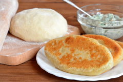 Heerlijke gebraden pastei op een plaat Deeg en deegrol op een keuken scherpe raad Kaas die met dille in een glaskom vullen Stock Foto
