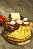 Heerlijke gevulde omelet op een houten raad Gebraden eiomelet met kersentomaten, knoflook en Spaanse peperpeper Voedzame breakf Stock Foto's