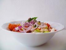 Heerlijke Griekse salade op een witte ceramische plaat Royalty-vrije Stock Foto's