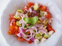 Heerlijke Griekse salade op een witte ceramische plaat van hierboven Royalty-vrije Stock Fotografie