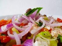 Heerlijke Griekse salade op witte ceramische plaat dichte omhooggaand Royalty-vrije Stock Afbeeldingen