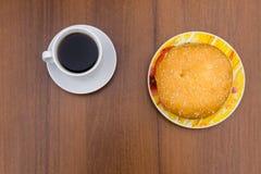 Heerlijke hamburger en kop van koffie op houten lijst Stock Fotografie