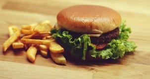 Heerlijke hamburger met gouden gebraden gerechten stock videobeelden