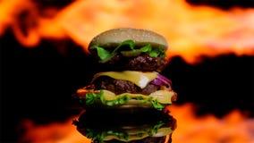 Heerlijke hamburger op het zwarte spiegeloppervlakte koken in vlam Royalty-vrije Stock Fotografie