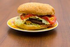 Heerlijke hamburger of sandwich op plaat op houten lijst Royalty-vrije Stock Fotografie