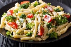 Heerlijke Italiaanse deegwaren Casarecce met broccoli, knoflook en tomaten in een romig sausclose-up op een plaat horizontaal stock foto's