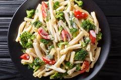 Heerlijke Italiaanse deegwaren Casarecce met broccoli, knoflook en tomaten in een romig sausclose-up op een plaat horizontale hoo royalty-vrije stock foto's