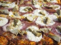 Heerlijke Italiaanse die pizza met ham en artisjokken, in de houten oven wordt gekookt stock foto