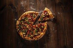 Heerlijke Italiaanse die pizza met plak op houten lijst wordt gediend Stock Afbeelding