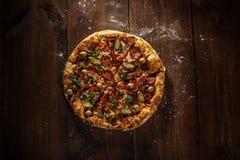 Heerlijke Italiaanse die pizza op houten lijst wordt gediend Royalty-vrije Stock Foto's