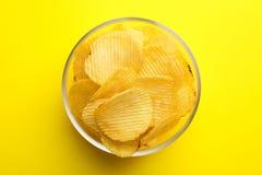 Heerlijke knapperige chips in kom op kleurenachtergrond royalty-vrije stock afbeeldingen
