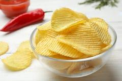 Heerlijke knapperige chips in kom op lijst royalty-vrije stock afbeelding