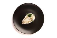 Heerlijke oester op een zwarte plaat Stock Foto
