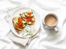 Heerlijke ontbijt of snack - rode kaviaar, avocadosandwiches en schimmelkaas op lichte achtergrond royalty-vrije stock foto's